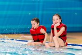 Happy Little Girls In A Red Vest Swimming In The Pool Of The Water Park. Child Learns To Swim. Teach poster