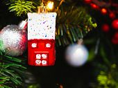 A Toy In The Form Of A Red House Hangs On A Christmas Tree. Christmas Tree Decoration In The Form Of poster