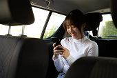 Asian Teenager Woman Using A Smartphone In Back Seat Of Car, Passengers Use An App To Order A Ride A poster