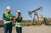Attractive Female Engineer And Foreman Discussing About Work Schedule Near An Oil Pumping Unit. Work poster