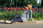 Pregnant Woman Sitting Near Tulip Flowerbed