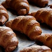 Close Up Of Freshly Baked Crusty Croissant On Buffet Line Background. A Tray With Fresh Croissant Br poster