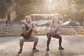Couple Exercise In Park. Training For Perfect Hips. Athletic Young Women And Man In Sportswear Doing poster