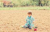 Little Helper In Garden. Boy Sit On Ground Planting Flower In Field. Fun Time At Farm. Gardening Con poster