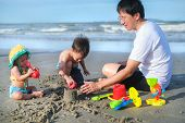 Asian Father Playing Sand With Baby Girl Daughter And Toddler Boy Son, Dad Playing Beach Toys With K poster