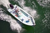 stock photo of outboard engine  - angles overhead view of an outboard powered small open fishing boat with one lone fisherman aboard - JPG