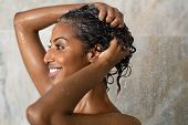 Woman washing hair showering in bathroom at home. Smiling black woman bathing while looking away. Ha poster