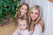 Mom And Daughters At The Christmas Tree. Christmas Season. Sisters. Merry Christmas And Happy Holida poster
