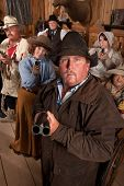 foto of gunslinger  - Heavyset gunslinger with shotgun in crowded old western saloon - JPG