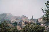 Village Of Speloncato In Corsica Shrouded In Mist poster
