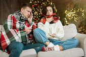 Sick Couple Both Wife And Husband Fall Ill Wrapped In Plaid And Scarf On The Sofa In Room Decorated  poster