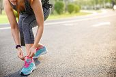 Woman Runner Tying Running Shoes Before Run For Exercise In The Morning. Woman Runner Checking Shoe  poster