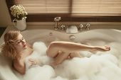 stock photo of bath tub  - Portrait of elegant beautiful woman relaxing in a spa bath - JPG