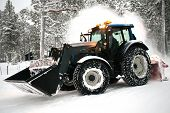stock photo of plowing  - closeup of snow plow vehicle cleaning winter road with big snow fountain - JPG