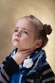 pic of throat  - Little girl with sore throat in flu season touching her neck - JPG