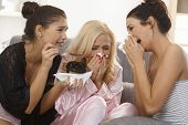Three female friends crying together at home, wearing pyjamas, blowing nose.