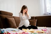stock photo of belly ache  - Pregnant woman worries above baby clothes at home on sofa - JPG