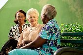 stock photo of sitting a bench  - Active retired elderly women and free time group of happy senior african american and caucasian female friends talking and sitting on bench in park - JPG