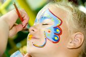 stock photo of school carnival  - Beautiful girl with blue eyes with painted butterfly on her face - JPG
