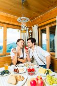 Couple in a traditional mountain hut having a meal, breakfasting with fruits, cold cuts, cheese and