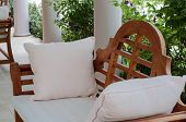 stock photo of bench  - outdoor wooden bench with white pillows in a garden - JPG