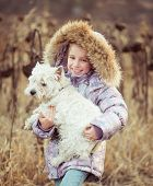 stock photo of westie  - happy girl with her dog  in a field in autumn - JPG