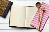 top view of old recipe book with kitchenware and napkin on white wooden table