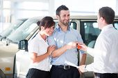 foto of arab man  - Happy couple getting car keys from a car seller - JPG