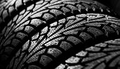 image of asymmetric  - winter car tyre on a black background - JPG
