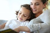stock photo of sofa  - Mom with little girl reading book in sofa - JPG