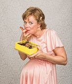 stock photo of finger-licking  - Happy expecting woman holding chocolates and licking fingers - JPG