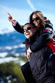 stock photo of piggyback ride  - Happy couple enjoying a piggyback ride in the mountains 