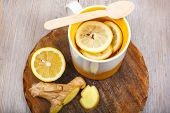 stock photo of home remedy  - Tea with lemon ginger and honey as natural medicine against flu - JPG