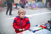 stock photo of flea  - Beautiful toddler boy in red clothes on flea market - JPG
