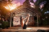 stock photo of ashtanga vinyasa yoga  - Yoga urdhva mukha paschimottanasana pose by fit man with dreadlocks on the beach near the fishermen hut in India - JPG