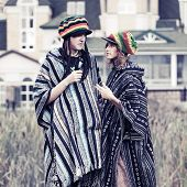 Young rastafarian couple in a poncho