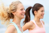 Running women runners training outdoors. Close up portrait of happy woman runner jogging outside wit