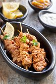 Tandoori chicken skewers, served with yogurt, lemon wedges and mango chutney.