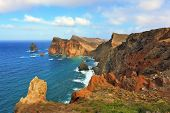 Eastern tip of the island of Madeira. Red and orange rocks cool grow out of foamy waves of the Atlan