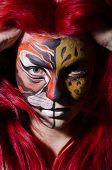 pic of face painting  - Woman with face painting in dark room - JPG