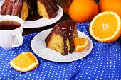 Piece of delicious cake  with oranges on table close-up
