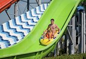 Father and son has into pool after going down water slide during summer