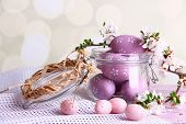 Composition with Easter eggs in glass jar and blooming branches on light background