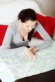 Young woman is searching something in map.