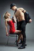 foto of striptease  - strong man show striptease for sexy woman in red - JPG