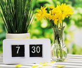 Digital alarm clock on table, on nature background