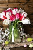 Composition with Easter eggs and beautiful tulips in glass jug on wooden background