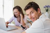 Happy young couple using laptop and cellphone at home
