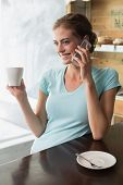 Smiling young woman drinking coffee while using mobile phone at counter in the coffee shop