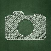 Travel concept: Photo Camera on chalkboard background